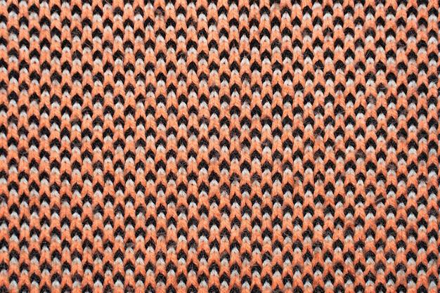 Synthetische gebreide stof met patroonelementen van rode, zwarte en witte garens van dichtbij. gebreide kleding