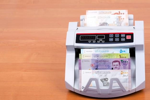 Syrisch geld in een telmachine op houten tafel