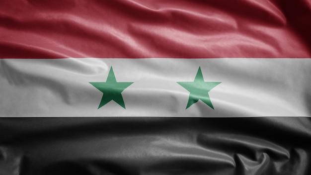Syrische vlag wappert in de wind. close-up van syrië sjabloon blazen, zachte en gladde zijde. doek stof textuur ensign achtergrond. gebruik het voor het concept van nationale dagen en landelijke gelegenheden