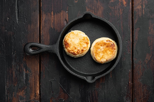 Syrniki cheese-pannenkoeken op gietijzeren koekenpan op gietijzeren koekenpan, bovenaanzicht plat, op zwarte houten tafel