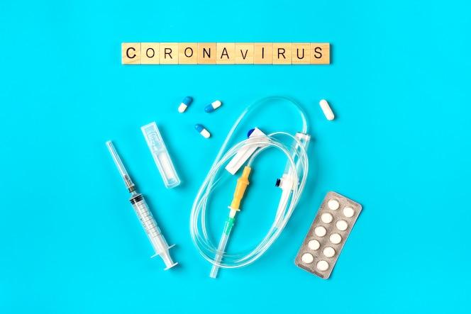 Systeem voor druppelaars, injectiespuit, pillen, hoestsiroop op blauw oppervlak. coronavirus woord. behandeling, preventie, vaccinatie tegen coronavirusconcept bovenaanzicht plat leggen