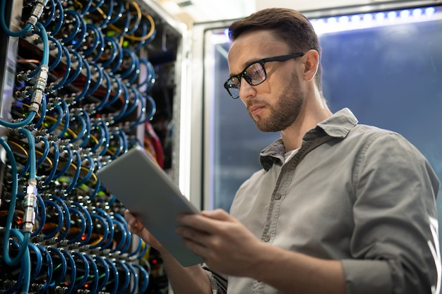 Systeemingenieur die tablet in serverruimte gebruiken