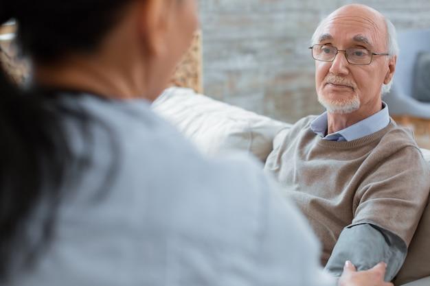 Systolische druk. arts met behulp van tonometer en peinzende kalme senior man helpen tijdens het controleren van zijn bloeddruk