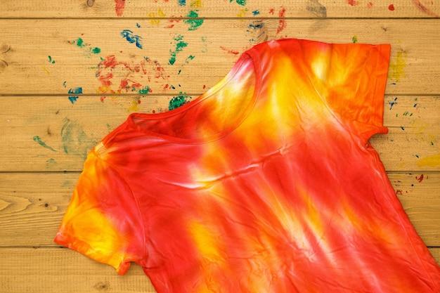 T-shirt geschilderd in de stijl van tie-dye op een houten tafel om te schilderen. kleurstof in tie-dye-stijl. plat leggen.