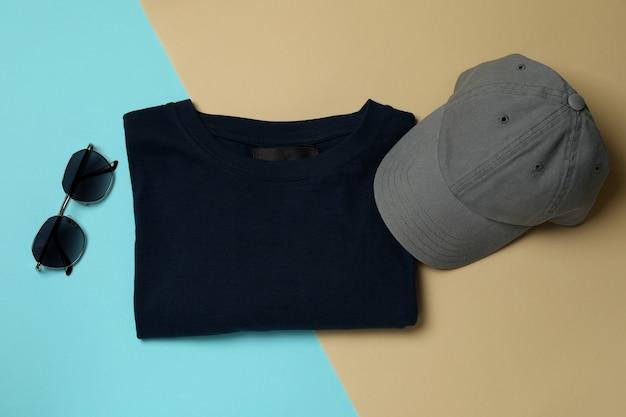 T-shirt, pet en zonnebril op tweekleurige achtergrond