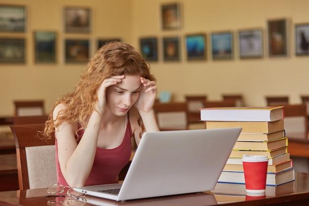 Taak-, test-, leer- en onderwijsconcept. het intelligente lezersmeisje dat terloops zittend aan bureau in leeszaal voor laptop draagt, houdt handen op voorhoofd, voorbereidend op belangrijk examen.