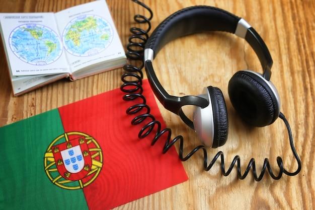 Taalcursus koptelefoon en vlag op houten tafel