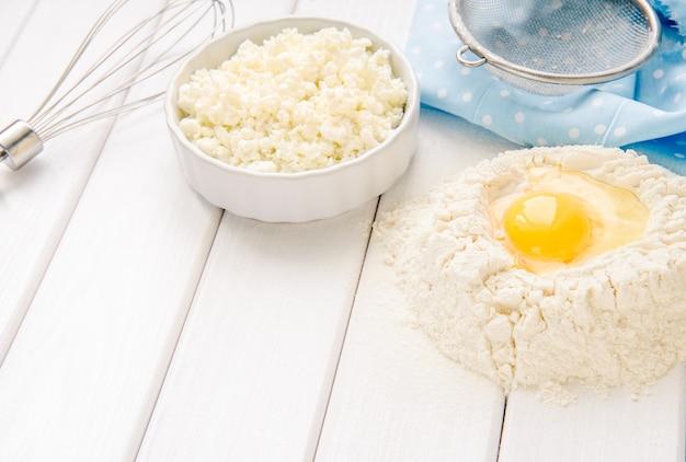 Taart bakken in rustieke keuken - deeg recept ingrediënten eieren, bloem, melk, boter, suiker op witte planken houten tafel van bovenaf