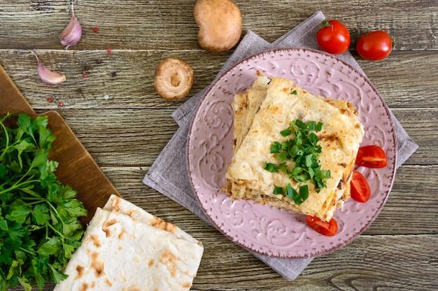Taart, braadpan pita met champignons, kwark en kaas op een plaat op een houten achtergrond. cake met lagen. het bovenaanzicht