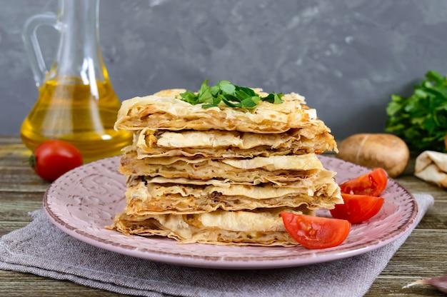 Taart, braadpan pita met champignons, kwark en kaas op een plaat op een houten achtergrond. cake met lagen.