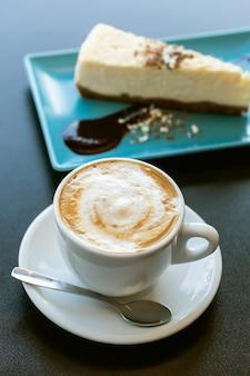 Taart en cappuccino koffie op de tafel