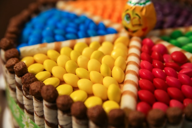 Taart gedecoreerd met gekleurde dragees, chocoladewafelbroodjes en snoep