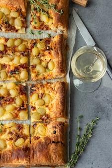 Taart gemaakt van bladerdeeg, gekarameliseerde ui, kaas, tijm en groene druif