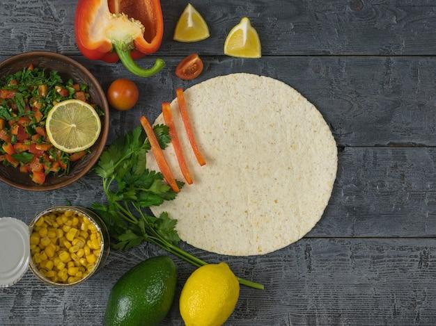 Taart gemaakt van maïsmeel, avocado, peper, tomaten, citroen, limoen, peterselie, maïs en kruiden