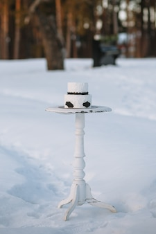 Taart in zwart-wit, staande op een standaard in een winterbos in de sneeuw