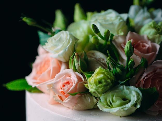 Taart is versierd met bloemen op een donkere.