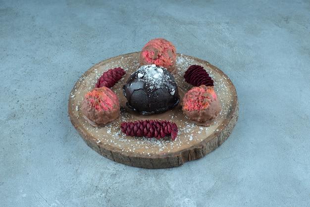 Taart, koekjes en dennenappels op een bord op marmer.