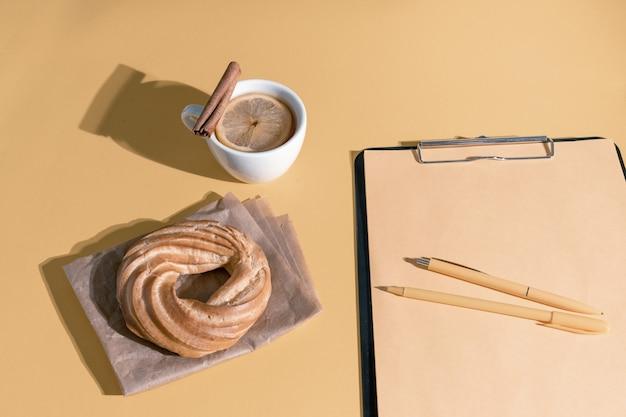 Taart, kopje thee of glühwein en hervat blad op de set zeil champagne kleur achtergrond, bovenaanzicht.