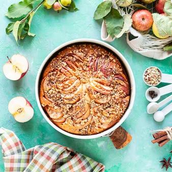 Taart met appels en ingrediënten op een groene steenachtergrond. bovenaanzicht.