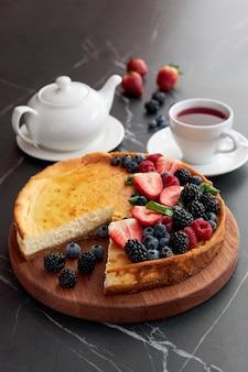 Taart met bessen met een aangesneden stukje met een kopje thee en theepot aardbeien bramen bosbessen