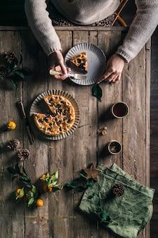 Taart met bessen op een houten tafel met een portie. de handen van vrouwen houden een bord met een fluitje van een cent. het uitzicht vanaf de top.