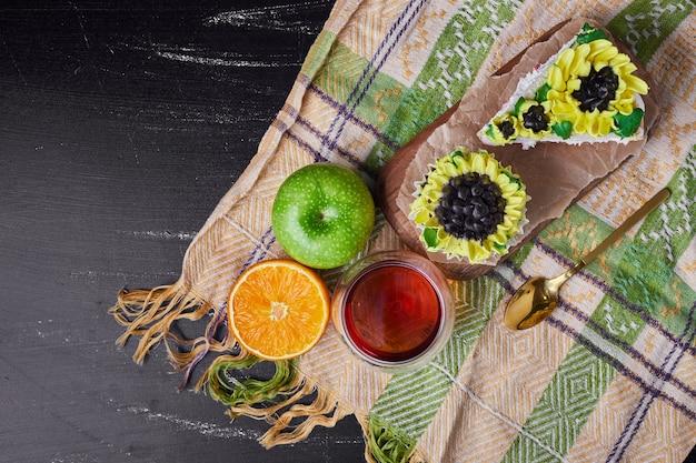 Taart met decoratie in zonnebloemstijl in een houten schotel met wijn.