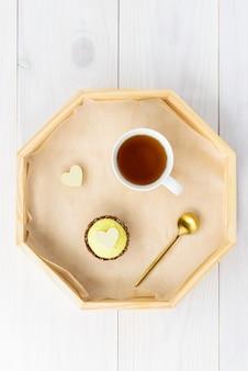 Taart met een kopje thee op een dienblad op een houten tafel