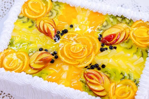 Taart met fruit en gelei. gesneden sinaasappel en kiwi. bovenaanzicht van exotisch dessert. op maat gemaakt zoetwarenproduct.