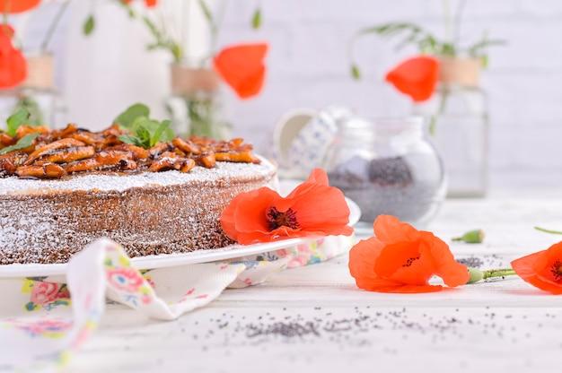 Taart met maanzaad op een witte achtergrond. huisgemaakt gebak en rode bloemen