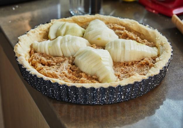 Taart met peren en perziken in metalen mal is klaar om te bakken in een elektrische oven.