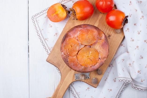 Taart met persimmon op een bruin houten bord op een witte achtergrond en een wit tafelkleed
