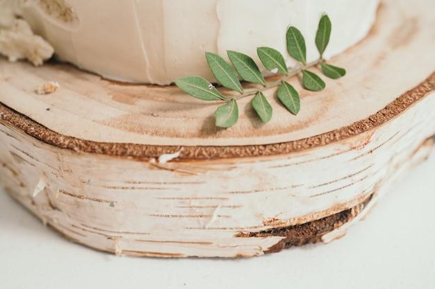 Taart met roomkaas versierd met eucalyptusbladeren handgemaakte zelfgemaakte cake houten dienblad van berken ...