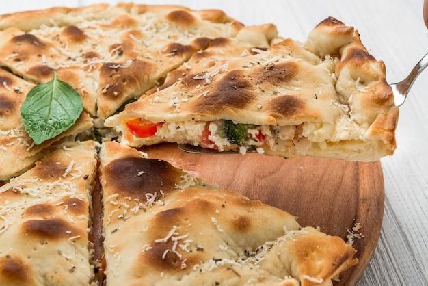 Taart met vlees, groenten en kaas op een houten oppervlak