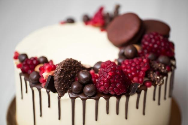 Taart met witte room, chocoladedruppels, granaatappel, noten en chocoladedecor
