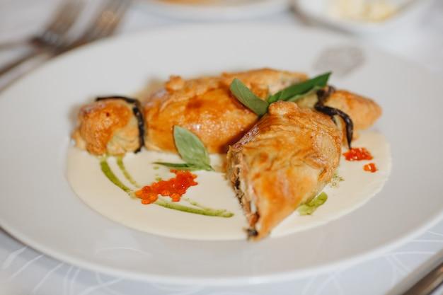 Taart met zuurkool en vis, russische kulebyaka. op een witte plaat en een houten tafel, achter een bruin tafelkleed, zijaanzicht schuin, dicht