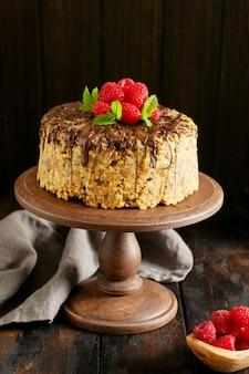 Taart mierenhoop versierd met frambozen, chocolade en noten op oude houten tafel. selectieve aandacht.