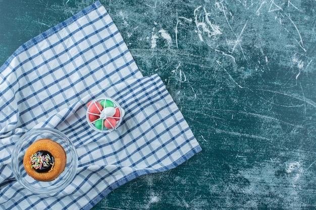 Taart op een glazen voetstuk naast chocolade in een kooi op de handdoek, op de blauwe achtergrond. hoge kwaliteit foto