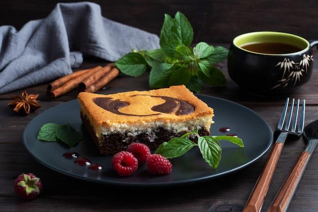 Taart op een plaat van chocoladebrownies en kwarktaart met frambozen.