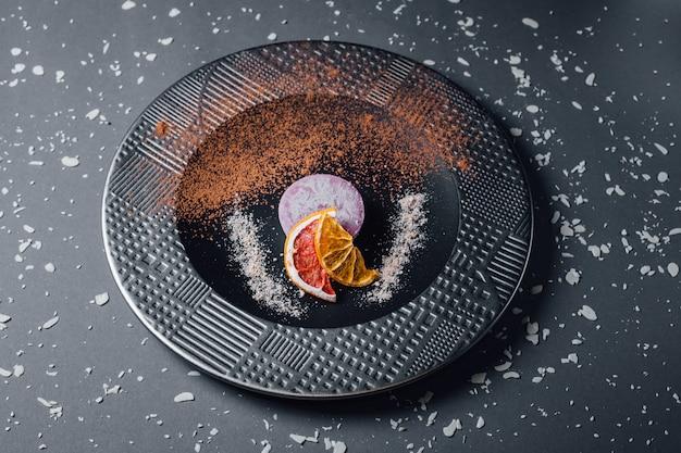 Taart. rauw vegetarisch dessert van gedroogde vruchten, noten en romige cashew-samenstelling, kokosboter, johannesbrood. op de plaat, geïsoleerd op zwarte achtergrond, close-up