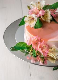 Taart versierd met bloemen. bruidstaart op een standaard op een witte houten achtergrond