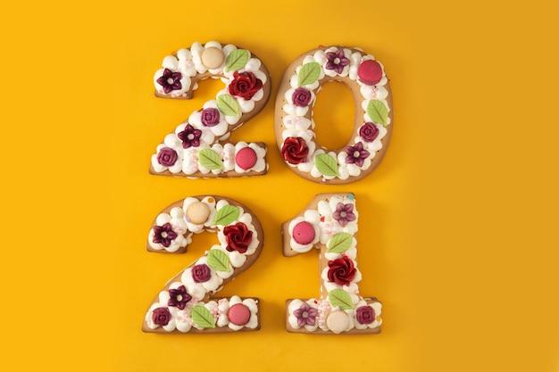 Taart versierd met bloemen geïsoleerd op gele achtergrond