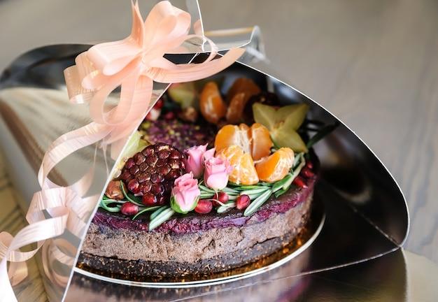 Taart versierd met vers fruit en bloemen