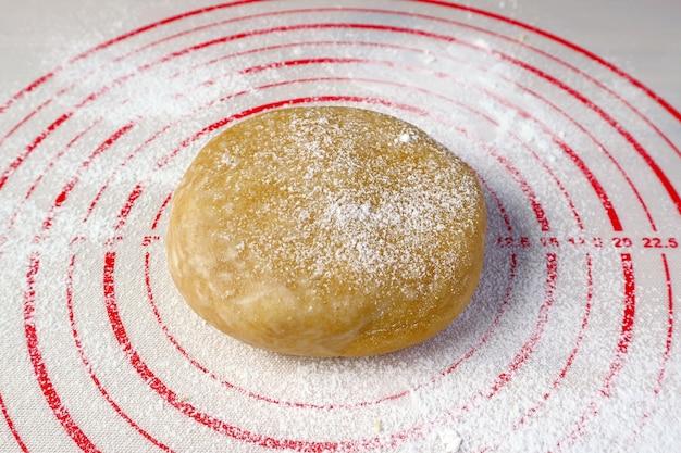 Taartdeeg geïsoleerd op een bakselmat voor het concept thuis bakken