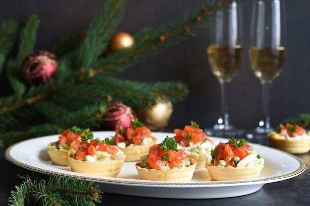 Taartjes gevuld met salade en zalm op een nieuwjaarstafel. feestelijke tafel met een glas champagne