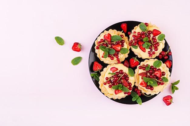 Taartjes met aardbeien, bessen en slagroom versierd met muntblaadjes, bovenaanzicht