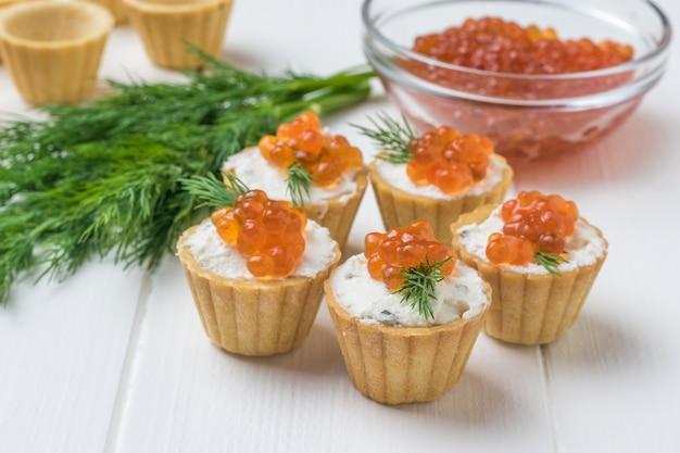 Taartjes met roomkaas en kaviaar op de muur van een glazen kom met rode kaviaar. voorgerecht met zeelekkernijen.