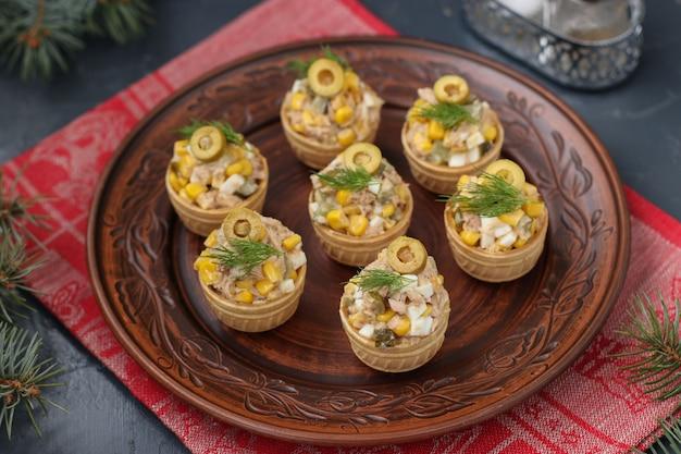 Taartjes met tonijn, maïs en eieren op een plaat op een donkere achtergrond, horizontaal formaat, close-up