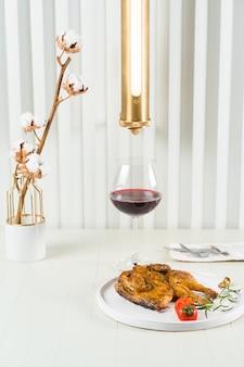 Tabakskip met een glas rode wijn, een vaas met katoenen takjes en een stijlvolle lamp