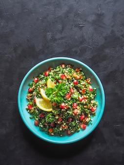Tabboulehsalade met couscous in een kom op de zwarte lijst. levantijnse vegetarische salade met peterselie, munt, bulgur, tomaat.