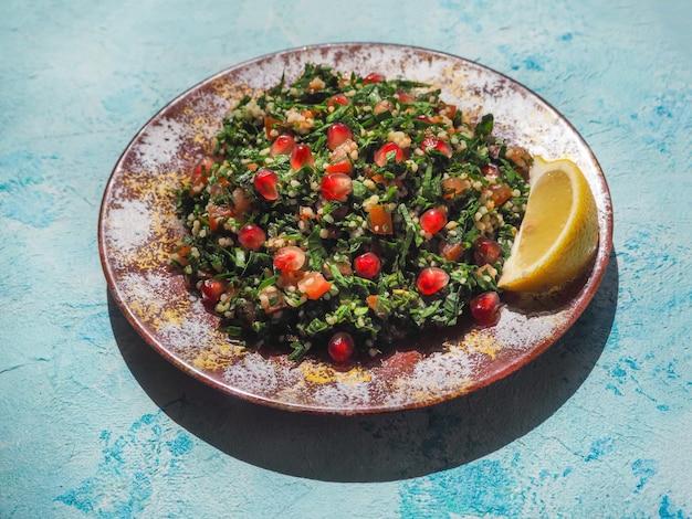 Tabboulehsalade met couscous in rode kom op blauwe rustieke lijst